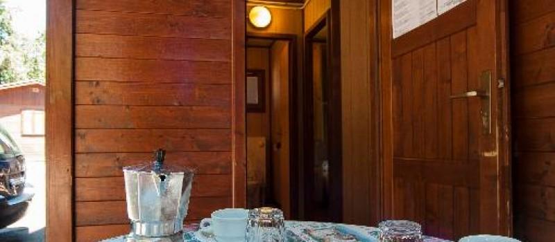 Chalet con bagno e cucina, camera matrimoniale, piccolo soggiorno con letto a castello e angolo cottura con frigorifero, bagno con doccia, wc e lavandino acqua calda, biancheria da bagno e da letto...